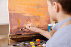 Gifted boy painting in the art studio. My artistic hobby. Young talented inspired boy sitting in the art studio and painting while expressing concentration and Royalty Free Stock Image