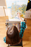 Gifted girl demonstrating her talent in the art studio. My vision of landscape. Talented sophisticated young girl sitting in studio and having art lesson while Stock Photos