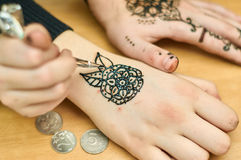 Gifted girl draws patterns by henna on the hands Royalty Free Stock Images