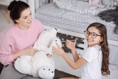 Gifted little child treating plush toy at home. Caring about favorite toy. Positive cheerful young mother sitting in the night nursery and holding plush toy Stock Photography