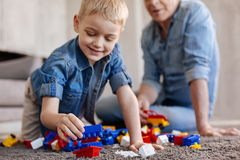 Gifted observant kid putting pieces together. Developing creativity. Talented beat creative boy reaching to some parts while playing with a construction set on Royalty Free Stock Photography