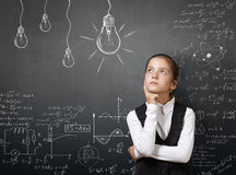 Gifted pretty young girl near blackboard with formulas. Stock Photo