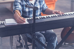 Gifted young handicap practicing music in the studio. Enjoying my hobby. Gifted young skilled handicap sitting in the wheelchair in the studio and enjoying free Stock Images