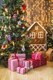 Giften in rode en witte verpakking onder de groene die Kerstboom met Kerstmisspeelgoed en kaarsen wordt verfraaid Royalty-vrije Stock Foto