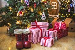 Giften in rode en witte verpakking onder de groene die Kerstboom met Kerstmisspeelgoed en kaarsen wordt verfraaid Royalty-vrije Stock Foto's