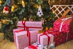 Giften in rode en witte verpakking onder de groene die Kerstboom met Kerstmisspeelgoed en kaarsen wordt verfraaid Stock Fotografie