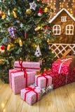 Giften in rode en witte verpakking onder de groene die Kerstboom met Kerstmisspeelgoed en kaarsen wordt verfraaid Stock Foto