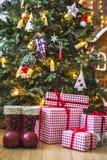 Giften in rode en witte verpakking onder de groene die Kerstboom met Kerstmisspeelgoed en kaarsen wordt verfraaid Stock Afbeelding
