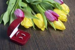 Giften voor gehouden van degenen Een boeket van gele en roze tulpen is verspreid op een donkere oppervlakte Dichtbij is een open  royalty-vrije stock afbeeldingen