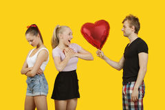 年轻对惊奇的妇女的人gifting的心形的气球有感觉左站立的朋友的后边 免版税库存图片