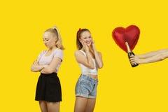 Gifting Herz des Mannes Handformte Ballon und Sektflasche zu überraschter Frau mit dem Freund, der linkes heraus hinten stehen gla Lizenzfreie Stockbilder