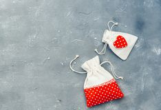 Gifting theme image with a checkered fabric pouch and a decorative red heart stock photos