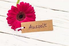 Giftkaart met Duits woord Auszeit, middelenonderbreking en roze bloesem op witte houten lijst stock foto's
