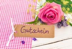 Giftkaart met Duits woord, Gutschein, middelenbon of coupon en mooi bloemenboeket stock foto's