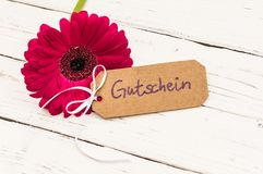 Giftkaart met Duits woord Gutschein, middelenbon en bloem op witte houten lijst stock foto