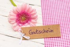 Giftmarkering met Duits woord Gutschein, middelenbon met roze bloem als gift voor de Dag van Valentin ` s of Moeder` s Dag royalty-vrije stock fotografie