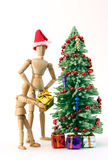 Gifts. Adult and child figurines putting gifts under a christmas tree against a white background Stock Photos