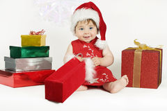 Gifts for Baby. A baby wearing a red dress and hat sits amongst a colourful array of gifts Stock Photo
