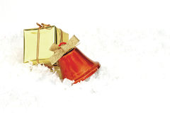 Gifts and bell close up. Colorful christmas gifts isolated of white snow Stock Images