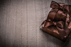 Gifts boxed in glittery paper with brown ribbons celebration con Royalty Free Stock Images