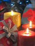 Gifts and Candles. Shot of three burning candles and a couple gifts. Christmas tree with blue lights used as a background. LOW LIGHT royalty free stock photo