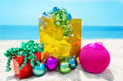 Gifts with Christmas ball on the beach Stock Images
