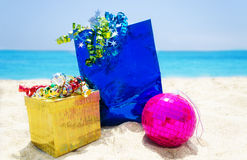 Gifts with Christmas ball on the beach Royalty Free Stock Photo