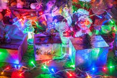 Gifts and Christmas decorations. Next to a glowing Christmas tree stock image