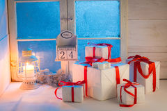 Gifts for Christmas with a frozen blue window and candlelight Royalty Free Stock Images