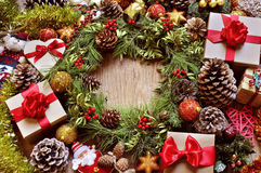 Gifts and christmas ornaments on a rustic wooden table. A rustic wooden table full of gifts, and christmas ornaments, such as a natural wreath with branches stock image