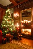 Gifts at the Christmas tree. Christmas evening by candlelight. classic apartments with a fireplace. Gifts at the Christmas tree. Christmas evening by royalty free stock image