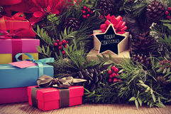 Gifts, christmas wreath and text merry christmas in a star-shaped signboard. A pile of gifts and a natural christmas wreath with pine cones and red berries, and royalty free stock image