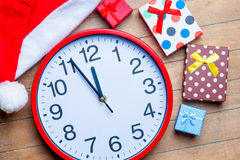Gifts, clock and santa claus hat on the wonderful brown wooden b Royalty Free Stock Image