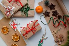 Gifts in craft paper, tied with red and green ribbon, surrounded by Christmas trifles stock photo
