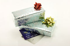Gifts and Credit Cards. Two shiny silver wrapped gifts with bows and two plastic credit cards on a white reflective background Stock Image