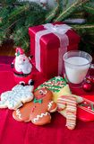 Gifts and cookies for Santa. Gifts and decorated sugar cookies for Santa, with a glass of cold milk Stock Photos