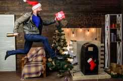 Gifts delivery. Man santa hat hurry to deliver gift on time. Christmas is coming. Spread happiness and joy. Bearded guy. In motion jump. Delivery christmas stock photo
