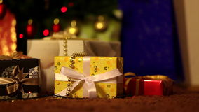 Gifts in front of christmas tree stock video