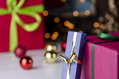 Gifts and glitter balls. Wrapped gifts contrasting with baubles and twinkles. The golden and emerald bowknots, as well as parts of the magenta paper, are within Stock Photos