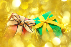Gifts on gold blurry lights background. Royalty Free Stock Photos