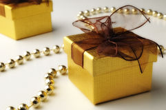 Gifts and golden pearls. With white background Stock Image