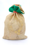 Gifts in gunny sack. The big brown gunny sack of Santa Claus filled with lots of christmas presents. Image isolated on white studio background Stock Image
