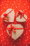 Gifts heart with red ribbon on a red background top view. Stock Image