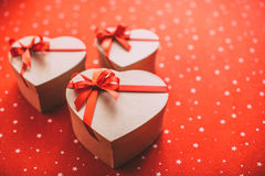 Gifts heart with red ribbon on a red background. Stock Images
