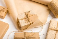 Gifts from Kraft paper on white table with threads and a roll. Gifts from Kraft paper on a white table with threads and a roll royalty free stock images