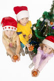 Gifts with love. Three young little caucasian blond girls standing together near christmas tree holding gifts and smiling sincerely.isolated over white Stock Photography