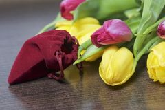 Gifts for loved ones. A bouquet of yellow and pink tulips is scattered on a dark surface. Nearby is an open velvet bag of red colo. R with gold jewelry Royalty Free Stock Photos