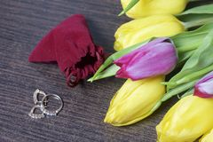 Gifts for loved ones. A bouquet of yellow and pink tulips is scattered on a dark surface. Nearby is an open velvet bag of red colo. R with gold jewelry Royalty Free Stock Images
