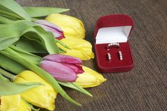 Gifts for loved ones. A bouquet of yellow and pink tulips is scattered on a dark surface. Nearby is an open velvet box of red colo. R with gold jewelry Stock Photography