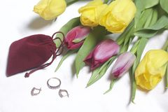 Gifts for loved ones. A bouquet of yellow and pink tulips is scattered on a light surface. Nearby is an open velvet bag of red col. Or with gold jewelry Stock Image
